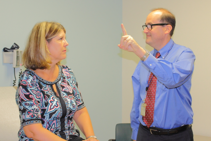 Dr. Andrew Feigin, MD, demonstrates a simple cognitive test to his colleague Jean Ayun, RN.