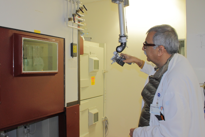 Dr. Vijay Dhawan demonstrates how radioactive materials can be handled safely with an elaborate mechanical manipulator.