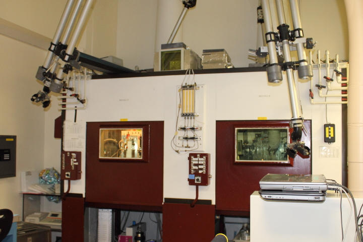 The radioactive products of the cyclotron are processed and measured in isolation, behind the thick glass windows of a