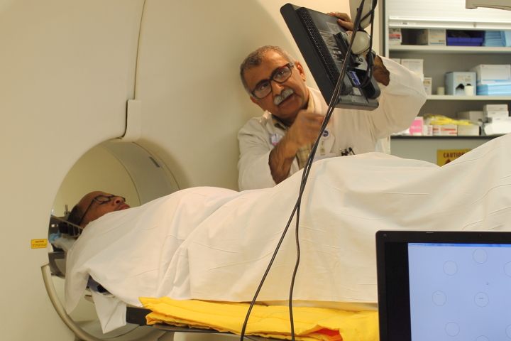 Dr. Vijay Dhawan points to the patient's monitor, where the patient can respond test images while a PET scan is made