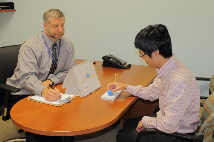 Dr. Paul J. Mattis, PhD, (left) demonstrates a tabletop test of cognitive functioning, administered to volunteers. His colleague Dr. Waturo Sato, MD, PhD, is posing as a stand-in test subject.